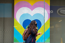 Glasgow, Scotland, UK. 12 March 2021. On the day Covid-19 lockdown is relaxed slightly in Scotland the city centre streets in Glasgow city centre remain almost Woman in facemark walks past heart poster in shop window. Iain Masterton/Alamy Live News