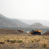 Reshaping of the waste rock pile and relocation of clean fill from shaft muck is ongoing at the Mount Taylor Mine. Contractors move dirt in the rain May 21 near the Village of San Mateo, which is visible in the distance.