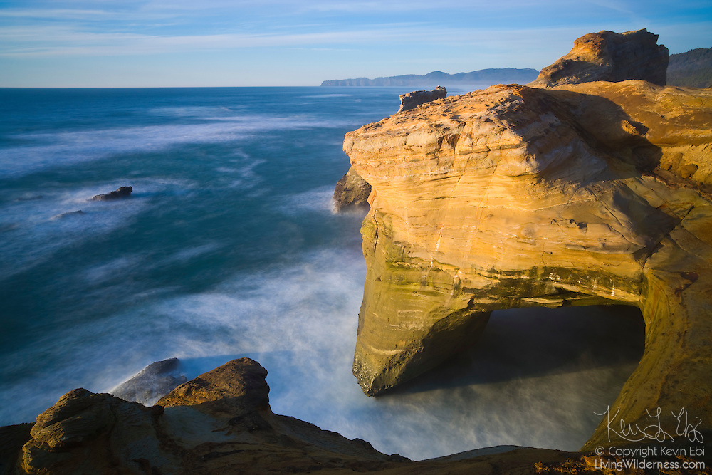 Pacific Ocean waves created an arch in the sandstone cliffs of Cape Kiwanda, near Pacific City, Oregon. The crashing waves are blurred by a 15-second exposure.