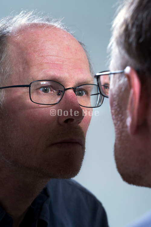 adult man staring at himself in the mirror