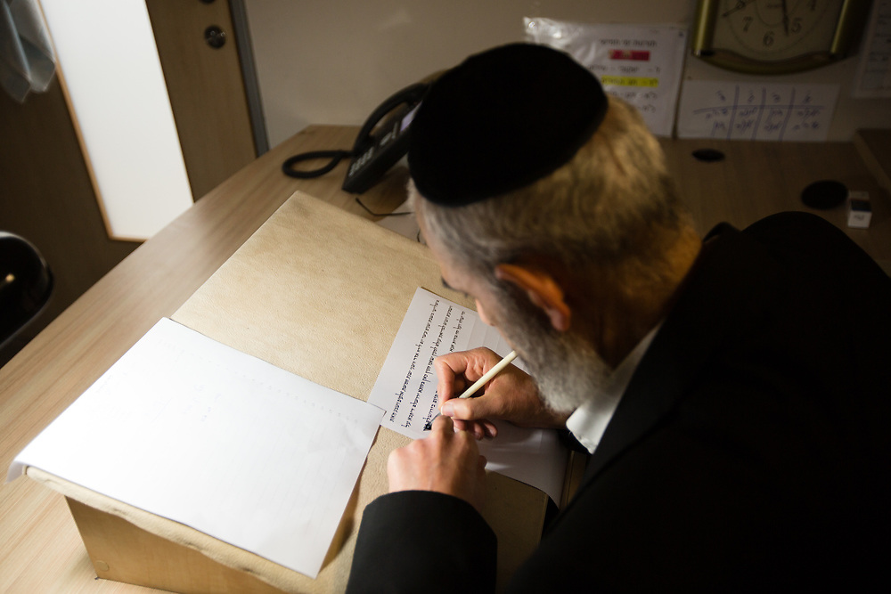 A scribe pens the letters for a get (or gett), a document in Jewish religious law which effectuates a divorce between a Jewish couple, at the Rabbinical Court in Jerusalem, Israel, on March 22, 2016.