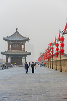 People walking atop the City walls near the South Gate of the Xi'an City Wall. It represents one of the oldest, largest and best preserved Chinese city walls.Xi'an is a large city and capital of Shaanxi Province in central China. It marks the Silk Road's eastern end and was home to the Zhou, Qin, Han and Tang dynasties' ruling houses.