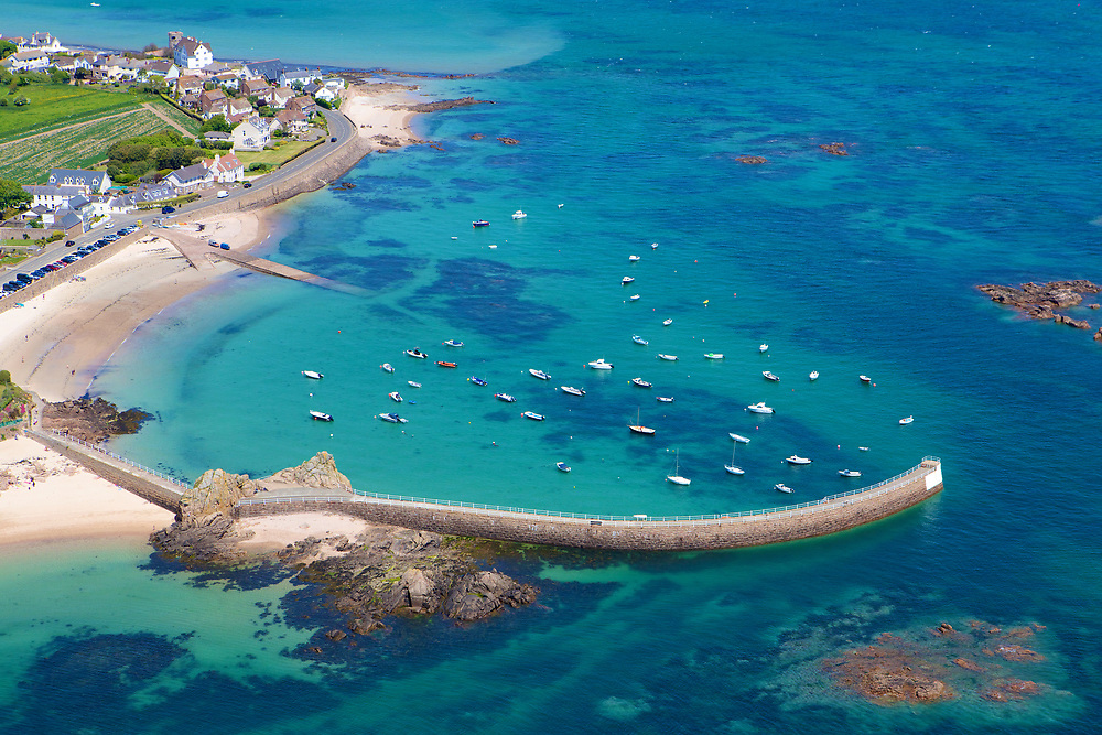 Aerial view of boats moored up next to the pier at La Rocque harbour, with its turquopise and clear water on a sunny day in Jersey, Channel Islands