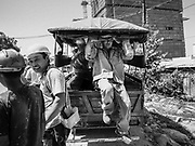 """15 FEBRUARY 2019 - SIHANOUKVILLE, CAMBODIA: A Chinese construction worker jumps out of a tuk-tuk that shuttles workers from their housing to the job site. There are about 80 Chinese casinos and resort hotels open in Sihanoukville and dozens more under construction. The casinos are changing the city, once a sleepy port on Southeast Asia's """"backpacker trail"""" into a booming city. The change is coming with a cost though. Many Cambodian residents of Sihanoukville  have lost their homes to make way for the casinos and the jobs are going to Chinese workers, brought in to build casinos and work in the casinos.      PHOTO BY JACK KURTZ"""