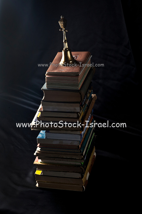 Dark and moody photograph of a stack of old worn vintage antique books against a dark black background