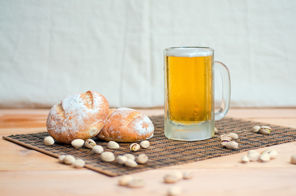 A mug of lager with bread and pistachios.