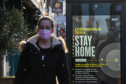 © Licensed to London News Pictures. 02/01/2021. London, UK. A woman wearing a protective face covering in north London walks past the government's 'Coronavirus Tier 4 - Stay Home' publicity campaign poster, after the mutated variant of the SARS-Cov-2 virus continues to spread around the country. The President of the Royal College of Physicians, Professor Andrew Goddard, has warned that COVID-19 infection cases are set to rise in the coming weeks and that NHS staff and healthcare workers are worried about the challenges against the virus over the coming months. Photo credit: Dinendra Haria/LNP