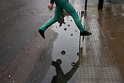 A man jumps over a puddle after rainfall in Oxford Street, central London.