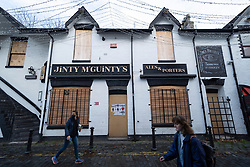 Glasgow, Scotland, UK.1 December 2020. Glasgow remains under level 4 lockdown and non essential businesses, bars and restaurants are closed. Pictured; Jinty McGuinty's bar in Ashton Lane in West End is closed and boarded up.  Iain Masterton/Alamy Live News