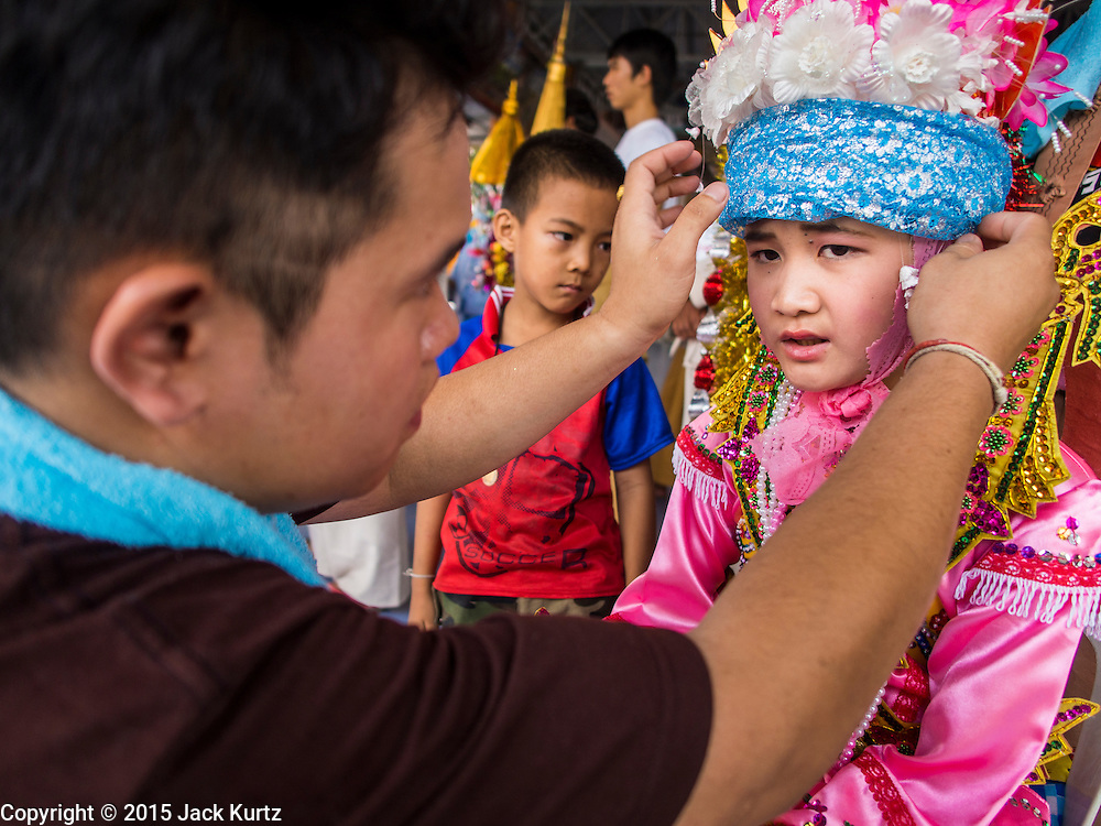 """04 APRIL 2015 - CHIANG MAI, CHIANG MAI, THAILAND:  A man helps a boy get into his ceremonial outfit for the Poi Sang Long Festival at Wat Pa Pao in Chiang Mai. The Poi Sang Long Festival (also called Poy Sang Long) is an ordination ceremony for Tai (also and commonly called Shan, though they prefer Tai) boys in the Shan State of Myanmar (Burma) and in Shan communities in western Thailand. Most Tai boys go into the monastery as novice monks at some point between the ages of seven and fourteen. This year seven boys were ordained at the Poi Sang Long ceremony at Wat Pa Pao in Chiang Mai. Poy Song Long is Tai (Shan) for """"Festival of the Jewel (or Crystal) Sons.     PHOTO BY JACK KURTZ"""