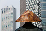 A Buddhist monk (usually not a real monk) collects alms outside Shinjuku Station with the Skyscrapers of West Shinjuku behind. Tokyo, Japan. Monday April 22nd 2019