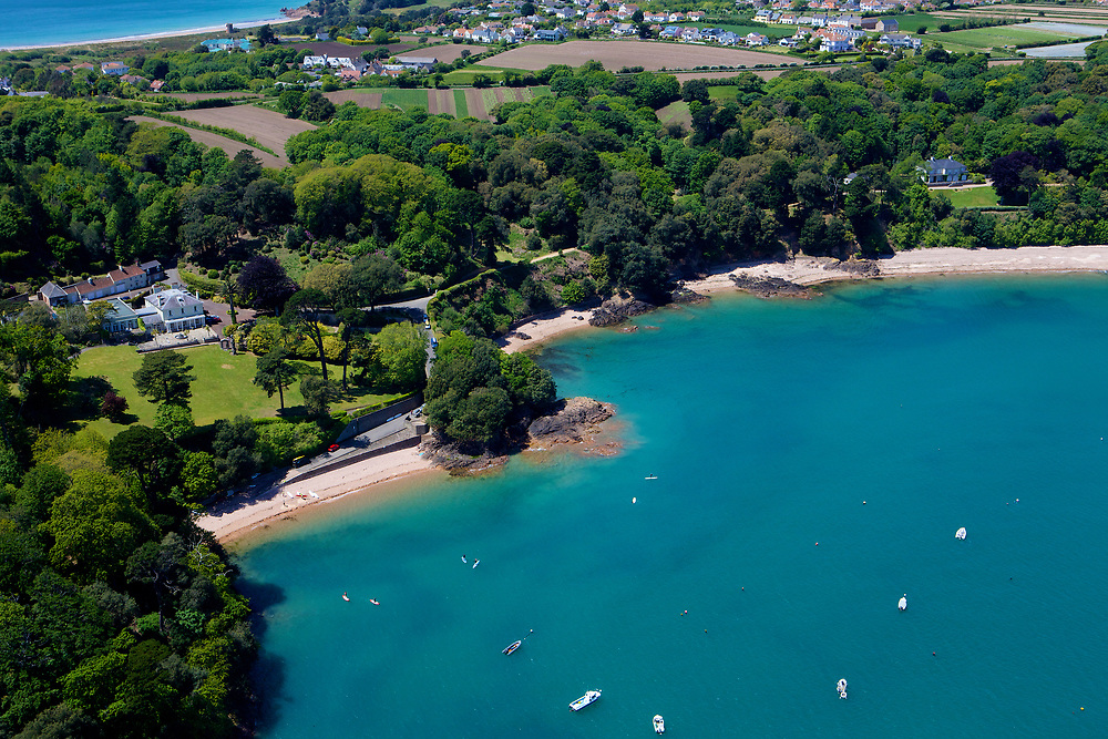Aerial view of boats acnhored up at Belcroute beach with its calm, turquoise water on a sunny summers day in Jersey, Channel Islands