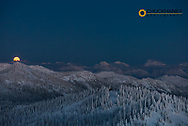 Full moon rises over snowy mountains from the summit of Big Mountain at Whitefish, Montana, USA