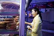 29 JUNE 2006 - PHNOM PENH, CAMBODIA: A woman sells baked goods from her van/bakery shop parked on Sisowath Quay, the main riverside boulevard in Phnom Penh, Cambodia. Photo by Jack Kurtz / ZUMA Press