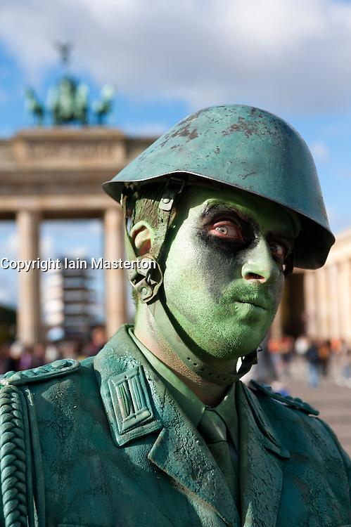 Mime artist dressed as an East German soldier performing in front of the Brandenburg Gate in Berlin