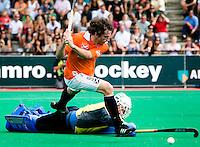 ROTTERDAM - Ronald Brouwer passeert doelman Johannes Blank van Uhlenhorst maar zal dit keer niet scoren, zondag tijdens de finale van de Euro Hockey League in Rotterdam tussen Bloemendaal en het Duitse UHC Hamburg (5-4).