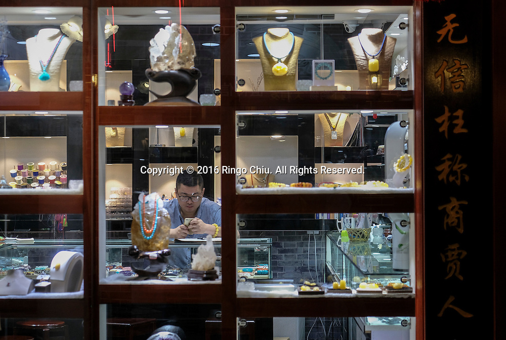 """A salesman at the1930 Folk Street, part of Shanghai Urban Planning Exhibition Center, in Shanghai, China. Shanghai is the most populous city in China and the most populous city proper in the world. It is one of the four direct-controlled municipalities of China, with a population of more than 24 million as of 2014. It is a global financial centre, and a transport hub with the world's busiest container port. Located in the Yangtze River Delta in East China, Shanghai sits on the south edge of the mouth of the Yangtze in the middle portion of the Chinese coast. The municipality borders the provinces of Jiangsu and Zhejiang to the north, south and west, and is bounded to the east by the East China Sea. A major administrative, shipping, and trading town, Shanghai grew in importance in the 19th century due to trade and recognition of its favourable port location and economic potential. The city was one of five forced open to foreign trade following the British victory over China in the First Opium War while the subsequent 1842 Treaty of Nanking and 1844 Treaty of Whampoa allowed the establishment of the Shanghai International Settlement and the French Concession. The city then flourished as a center of commerce between China and other parts of the world (predominantly Western countries), and became the primary financial hub of the Asia-Pacific region in the 1930s. However, with the Communist Party takeover of the mainland in 1949, trade was limited to socialist countries, and the city's global influence declined. In the 1990s, the economic reforms introduced by Deng Xiaoping resulted in an intense re-development of the city, aiding the return of finance and foreign investment to the city. Shanghai has been described as the """"showpiece"""" of the booming economy of mainland China; renowned for its Lujiazui skyline, museums and historic buildings, such as those along The Bund, the City God Temple and the Yu Garden.(Photo by Ringo Chiu/PHOTOFORMULA.com)<br /> <br /> Usage Notes:"""