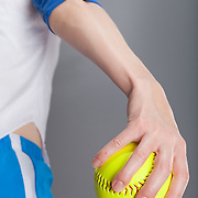 Closeup on a woman's hand holding a softball that she is about to throw. Photographed with studio lighting in front of a gray backdrop.