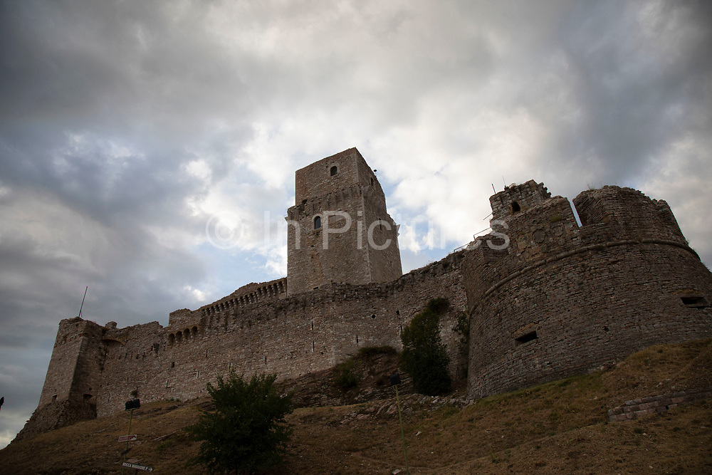 Rocca Maggiore in Assisi, Umbria, Italy. The Rocca Maggiore dominated the citadel of Assisi and the valley of Tescio, for more than eight hundred years as a fortress for their defense. Assisi is a town in the Province of Perugia in the Umbria region, on the western flank of Monte Subasio. It is generally regarded as the birthplace of the Latin poet Propertius, and is the birthplace of St. Francis, who founded the Franciscan religious order in the town in 1208, and St. Clare, Chiara dOffreducci, the founder of the Poor Sisters, which later became the Order of Poor Clares after her death. Assisi is now a major tourist destination for those sightseeing or for more religious reasons.