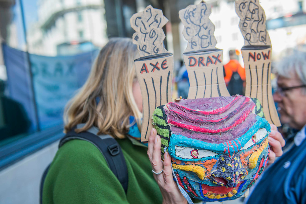 A mother holds up a mask, made by her daughter, to on-coming traffic while she discusses the issues with a passer-by - #AxeDrax protest outside the annual Drax shareholder AGM. Protestors demanded cleaner, greener energy generation systems. They continued on to the Department of Energy and Climate Change to deliver a petition demanding that subsidies given to Drax, for burning biomass, be stopped for making climate change worse.