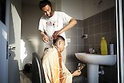 Un ragazzo si improvvisa barbiere nel bagno di una delle ex palazzine olimpiche.