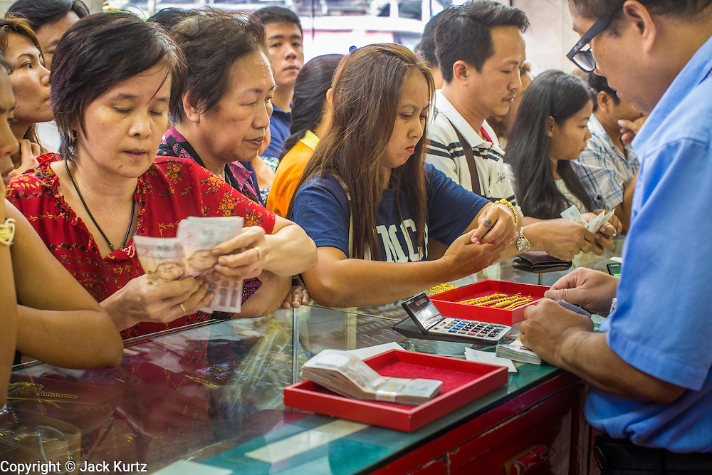17 APRIL 2013 - BANGKOK, THAILAND: A Thai woman counts out cash before buying gold in a Bangkok gold shop. Thais flocked to gold shops in Bangkoks's Chinatown this morning to buy gold. Wednesday was the first day most gold shops were open after a five day holiday weekend. Shops were closed Friday through Tuesday, when global gold prices dropped by more than 13% based on jitters that Cyprus might liquidate its gold stocks. The Thailand Futures Exchange (TFEX) suspended trading of all gold and silver futures for a short time Tuesday morning because of instability in the market. Gold is now about 22 percent below the record peak of $1,920.30 an ounce set in September 2011. Thais buy gold as both jewelry and an investment, a hedge against inflation and financial failures. Bangkok's Chinatown district is the center of Thailand's gold trade.    PHOTO BY JACK KURTZ