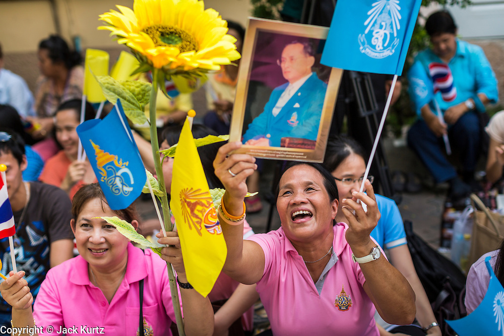 """01 AUGUST 2013 - BANGKOK, THAILAND: Thais wave pictures of Bhumibol Adulyadej, the King of Thailand, and the yellow flag of the monarchy while they chant """"Long Live the King"""" at Siriraj Hospital before the King, 85, was discharged from Bangkok's Siriraj Hospital, Thursday where he has lived since September 2009. He traveled to his residence in the seaside town of Hua Hin, about two hours drive south of Bangkok, with his wife, 80-year-old Queen Sirikit, who has also been treated in the hospital for a year.      PHOTO BY JACK KURTZ"""