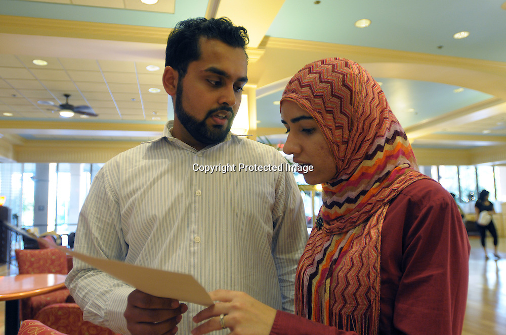 Atif Irfan, left, and his wife, Sobia Ijaz, go over their itinerary for a seminar at a religious conference at the Regal Sun Resort in Lake Buena Vista, Fla., Friday, Jan. 2, 2009.  Both Irfan and Ijaz were not allowed to board an AirTran flight from Washington, D.C. to Orlando after passengers mistook a conversation their group had about the safest place to sit aboard their plane. (Photo by Phelan M. Ebenhack)