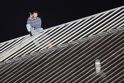 © Licensed to London News Pictures . 14/09/2015. Manchester, UK. An inmate at HMP Manchester ( Strangeways Prison ) , identified locally as STUART HORNER , talks through smashed skylights , after climbing a fence and on to the roof , in protest at conditions inside . Photo credit : Joel Goodman/LNP