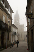 An old man walks with a cane up an empty street in Sarria, Galicia, Spain. A church steeple is visible through the mist in the background.