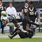 UCF Knights linebacker Titus Davis (10) makes a tackle on South Florida Bulls wide receiver Tyre McCants (8) during a NCAA football game between the University of South Florida Bulls and the UCF Knights at Spectrum Stadium on Friday, November 24, 2017 in Orlando, Florida. (Alex Menendez via AP)