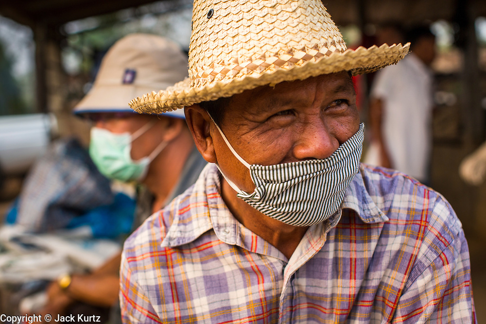 """06 APRIL 2013 - CHIANG MAI, CHIANG MAI, THAILAND: Men wear face masks to cut the amount of smoke and pollutants they breathe in Chiang Mai, Thailand. The """"burning season,"""" which roughly goes from late February to late April, is when farmers in northern Thailand burn the dead grass and last year's stubble out of their fields. The burning creates clouds of smoke that causes breathing problems, reduces visibility and contributes to global warming. The Thai government has banned the burning and is making an effort to control it, but the farmers think it replenishes their soil (they use the ash as fertilizer) and it's cheaper than ploughing the weeds under.   PHOTO BY JACK KURTZ"""