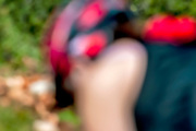 Out of focus female cyclist cycling in nature on a single track path in a forest. Photographed in Israel in February