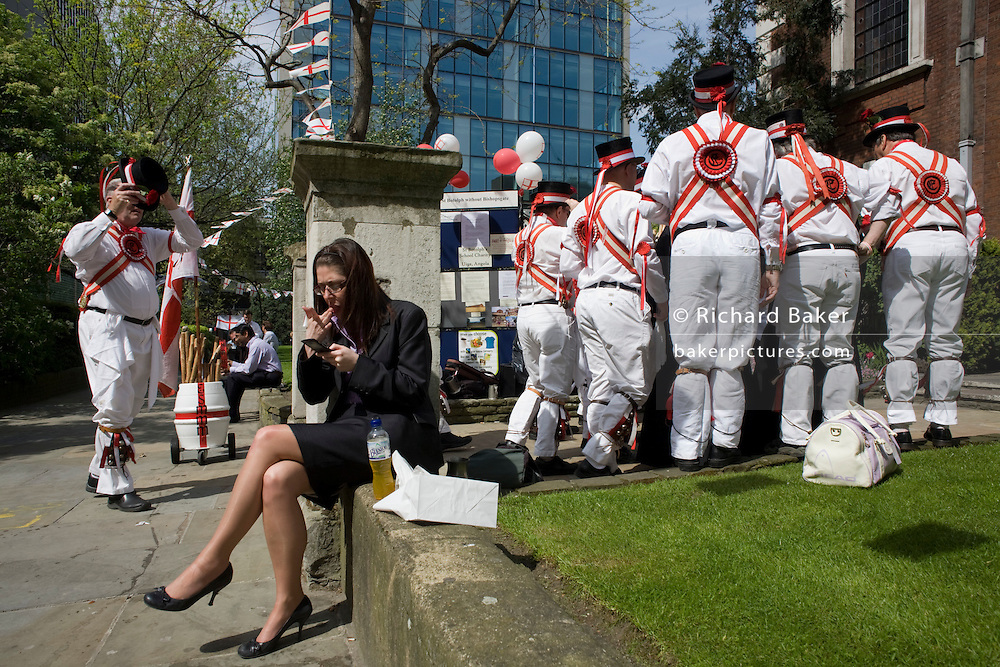A lady office worker trying to enjoy her lunchtime in spring sunshine, ignores a traditional band of Morris Men who gather to begin a St George's Day performance at the church of St. Botolph's without Bishopsgate in the City of London. Wearing white uniforms they jig their traditional dance, a form of English folk dance accompanied by accordion and pipes. It is based on rhythmic stepping and the execution of choreographed figures by a group of dancers. Implements such as sticks, swords, and handkerchiefs may also be wielded by the dancers. In a small number of dances for one or two men, steps are performed near and across a pair of clay tobacco pipes laid across each other on the floor. English records of Morris dancing date back to 1448.