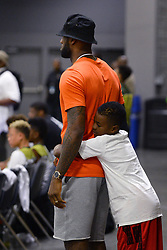 July 21, 2017 - Charlotte, NC, USA - LeBron James watches his son, LeBron Jr.'s team during youth tournament action at the Charlotte Convention Center in Charlotte, N.C., on Friday, July 21, 2017, as son, Bryce James, right, gives him a hug from behind. (Credit Image: © Jeff Siner/TNS via ZUMA Wire)