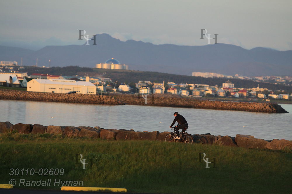 Man rides bicycle on coastal path in Seltjarnarnes late on a summer evening in Reykjavik, Iceland.