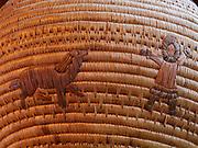 Figure of dog playing with child on large antique Yupik Eskimo grass basket from Western Alaska.