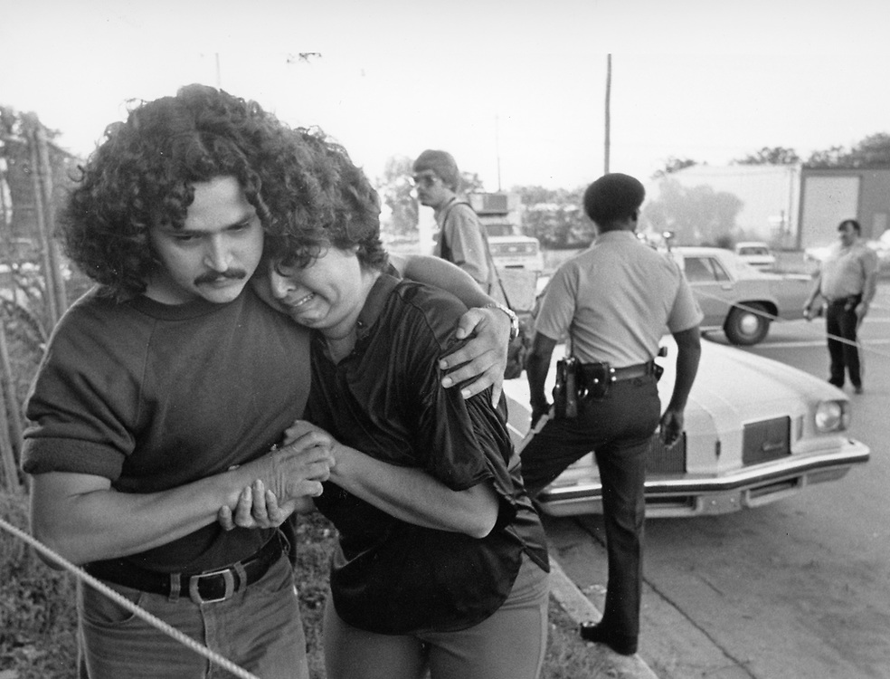©1981 wife of accident victim leaves the scene and is comforted by unknown person.