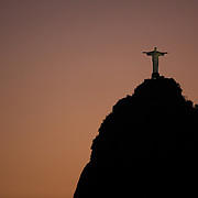 The iconic Cristo Redentor, Christ the Redeemer statue at sunset atop the mountain Corcovado shot from Suger Loaf Mountain. The Christ statue was voted one of the seven wonders of the modern world in 2007. It was designed by Brazilian Heitor de Silva Costa and was inaugurated in 1931 having taken years to assemble. Rio de Janeiro, Brazil. 21st July 2010. Photo Tim Clayton..