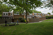 A father and daughter, who live opposite the estate, play table tennis in Cressingham Gardens on 30th May 2015 in South London, United Kingdom. Cressingham Gardens is a council garden estate, located on the southern edge of Brockwell Park. It comprises of 306 dwellings and built to the design of Lambeth Borough Council architect Edward Hollamby in the early 1970s. In 2012, Lambeth Council proposed regeneration of the estate, a decision highly opposed by many residents. Since the announcement, the highly motivated campaign group Save Cressingham Gardens has been active.
