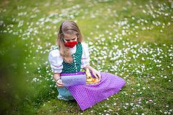 THEMENBILD - Ein Mädchen in Trachtund mit NMS-Maske mit einem Osternest und Schokolade-Hasen auf einer Blumenwiese, aufgenommen am 10. April 2020, in Graz // a girl in traditional austrian dress and a face mask is seeking for a easter present in a flower meadow on 10 April 2020. EXPA Pictures © 2020, PhotoCredit: EXPA/ Erwin Scheriau