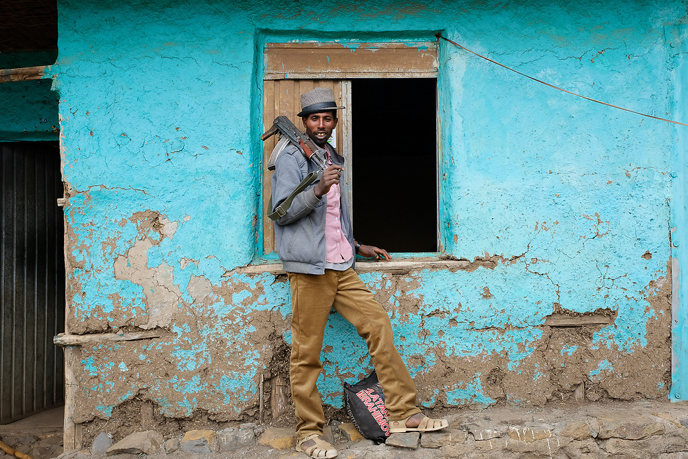 A young accompanying scout poses with his Kalashnikov on a wall of the community lodge in geech at the altitude of 3600mt in the Simien mountains national park. To trek in the national park, being accompanied by an armed local is mandatory.