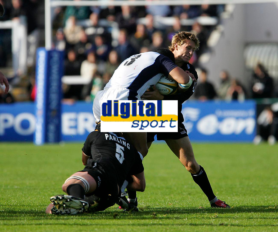 Photo: Andrew Unwin.<br /> Newcastle Falcons v Sale Sharks. Powergen Cup.<br /> 02/10/2005.<br /> Sale's Elvis Sevalai'l (C) is tackled by Newcastle's Jonny Wilkinson (R).