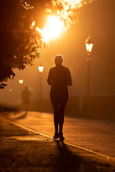 © Licensed to London News Pictures. 27/09/2018. London, UK. A jogger in Hyde Park at sunrise this morning. The temperature in the capital is set to reach 22 degrees Celsius later today. Photo credit : Tom Nicholson/LNP