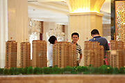 Potential buyers look at models of apartment buildings at the sales office of the Huading Stars City in Yangzhou, Jiangsu Province, China on 19 July 2012. While the Chinese government has tried various ways to cool down the property market, real estate prices have still seen a steady increase in recent years, proving hard for the country to move away from an investment driven economy.