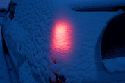 A glowing rear car indicator light shines through freshly-fallen snow at dawn in a South London street.