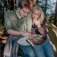 Hikers consult a map while hiking in Redwood Regional Park in Contra Costa County, above Oakland, California.