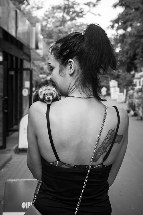 A Ukrainian woman walks on a sidewalk with her pet ferret in the port city of Mariupol.