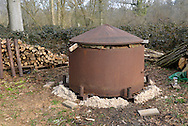 A charcoal kiln loaded and ready for lighting in a deciduous woodland in southern England