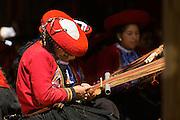 Local Quechua woman wearing traditional dress weaving at Chinchero Town Sunday Market, Cusco region, Peru, South America